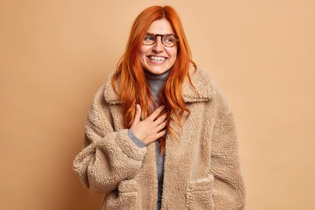 Dolblij roodharige volwassen vrouw lacht en drukt gelukkige oprechte emoties uit, draagt een bril en een warme bruine bontjas, geconcentreerd opzij met een glimlach, geniet van de wintertijd heeft een opgewekte stemming. mode concept