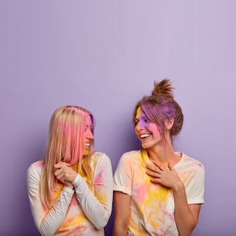 Dolblij, tevreden vrouwen hebben holi-kleurenfeest, spelen samen grapjes, lachen positief, genieten van lentevakantie, kijken elkaar aan, geïsoleerd over paarse muur met lege ruimte erboven.