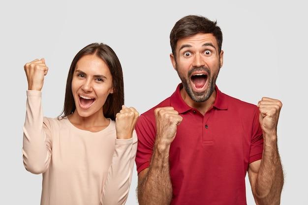 Dolblij twee vrouwen en mannen heffen vuisten met triomf, hebben een succesvolle deal