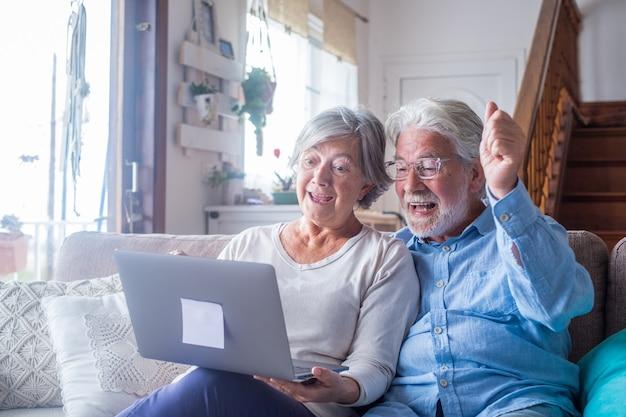 Dolblij volwassen familiepaar van middelbare leeftijd kijken naar laptopscherm, vieren online loterijwinst of veilingbod, opgewonden van het lezen van e-mail met geweldig nieuws, samen geluk thuis voelen.