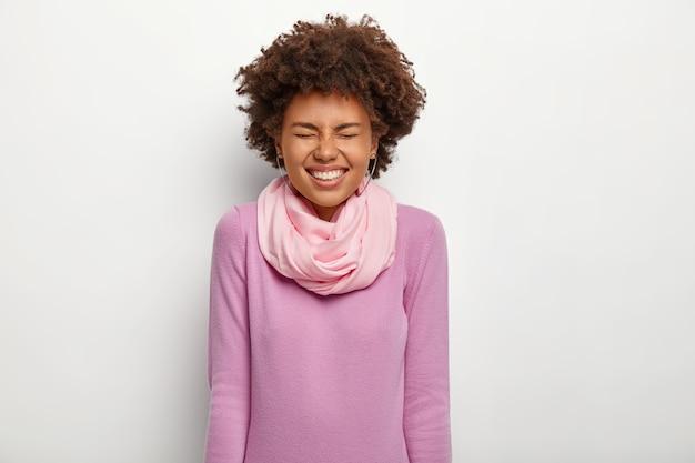 Dolblij vrouw met donkere huid houdt ogen gesloten, lacht vrolijk, draagt paarse coltrui met zijden sjaal, heeft een brede glimlach
