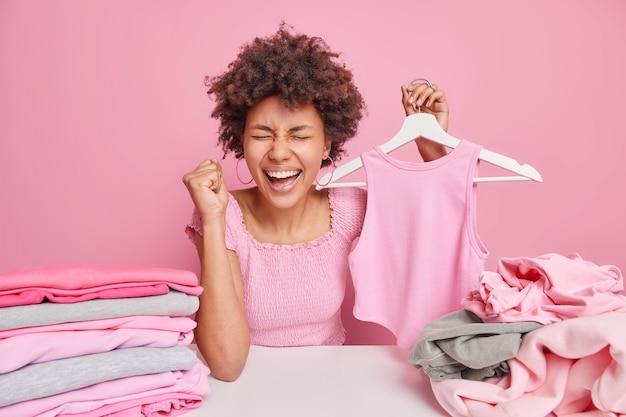 Dolblij vrouw met donkere huid met krullend haar cleches vuist van geluk houdt kleding op hanger zit aan tafel plooien wasserij geïsoleerd over roze muur