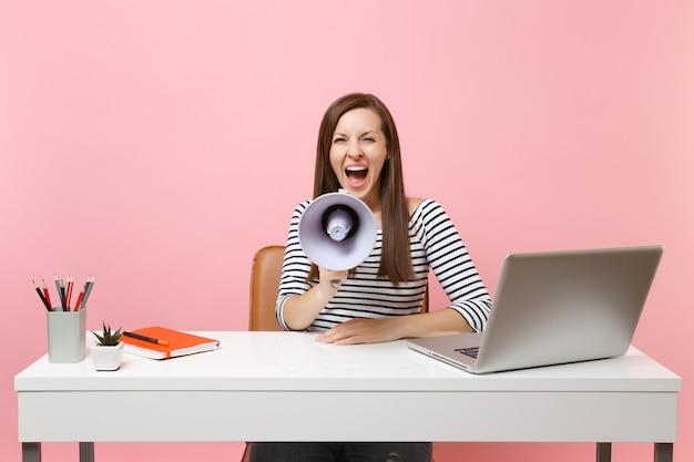 Dolblij vrouw schreeuwen in megafoon terwijl zitten en werken aan project op witte bureau op kantoor met pc-laptop geïsoleerd op pastel roze achtergrond. prestatie zakelijke carrière concept. ruimte kopiëren.