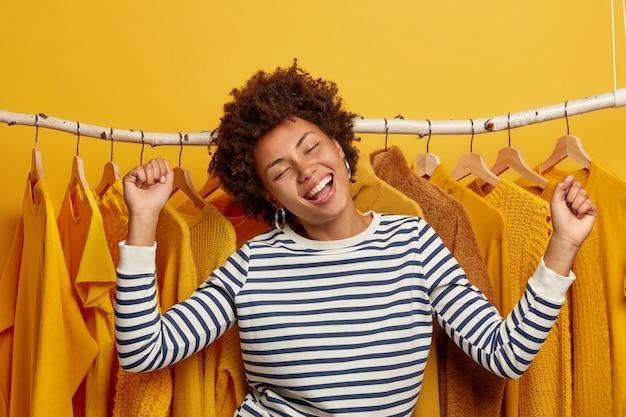 Dolblij vrouw shopaholic maakt overwinning tegen kledingrek, blij om verschillende kleding te kopen, kantelt het hoofd