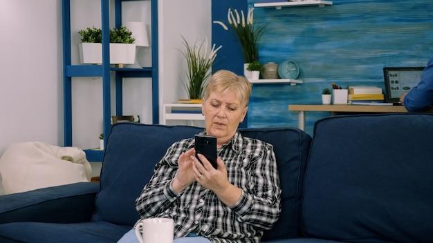 Dolblij vrouw van middelbare leeftijd zittend op de bank in de woonkamer praten over video-oproep op smartphone gadget, blij opgewonden senior vrouwelijke groet spreken op web met behulp van smartphone, technologie concept