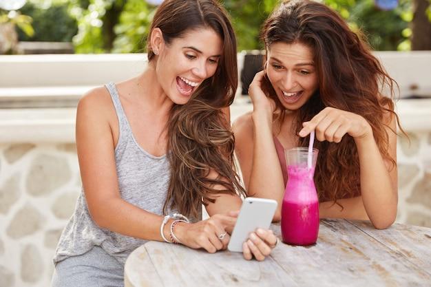 Dolblij vrouwelijke tavelers of bloggers updaten multimedia, blij om veel reacties en volgers te zien