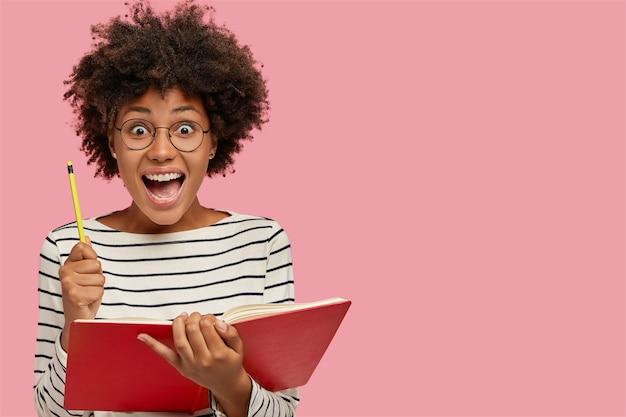 Dolblij zwarte vrouw houdt leerboek en potlood vast, roept met verbazing uit