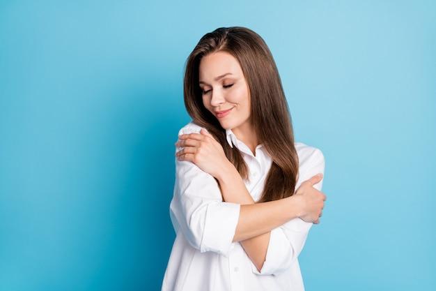 Dolblije dame die zichzelf omhelst armen ogen gesloten positieve aangename gevoelens draag wit overhemd geïsoleerd blauwe kleur achtergrond