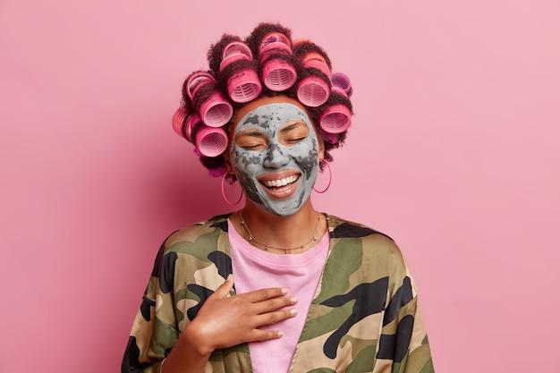 Dolblije mooie vrouw lacht vrolijk sluit de ogen glimlacht in grote lijnen drukt positieve gevoelens uit geniet van schoonheidsprocedures thuis bereidt zich voor op date past haarrollers toe voor perfect kapsel