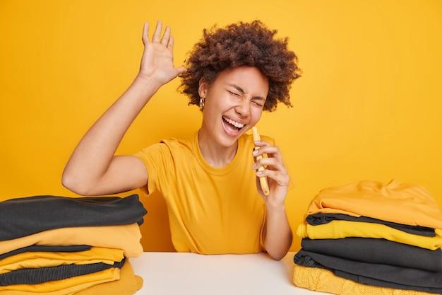 Dolblije vrouw met donkere huidskleur heft palm op zingt lied houdt smartphone vast alsof microfoon aan tafel zit met opgevouwen wasgoed geïsoleerd over gele muur. drukke vrouw vouwt kleren na het wassen