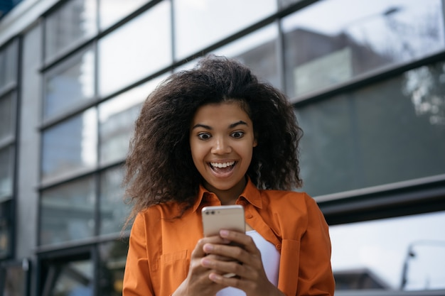 Dolblije vrouw met smart met mobiele app voor online winkelen, eten bestellen