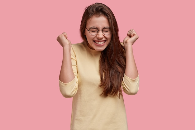 Dolblije vrouw steekt gejuich met gebalde vuisten op, geniet van succes en triomf, draagt een bril en casual outfit, modellen boven roze ruimte