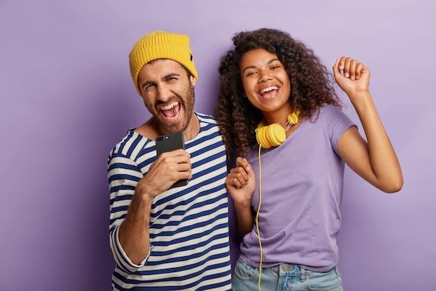 Dolgelukkig gemengd ras duizendjarige vrouw en man hebben samen plezier, zingen luid en dansen op muziek, gebruiken moderne technologieën voor entertainment