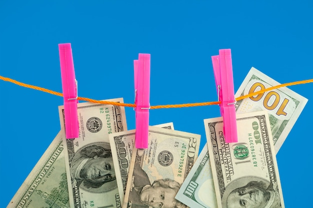 Dollar geld op touw wasknijper op blauwe achtergrond