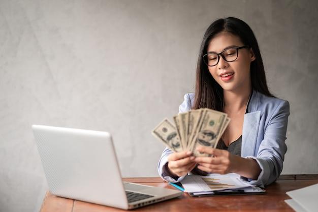 Dollar in de hand van een onderneemster. een aziatische vrouw werkt vanuit huis of op kantoor en is blij om dollargeld te krijgen van haar werk en van een aanvullende carrière of parttime zelfstandige.