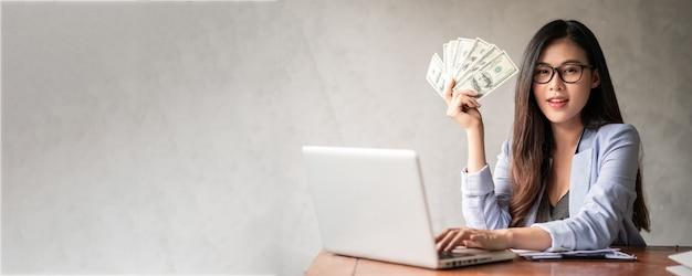 Dollar in de hand van een zakenvrouw. een aziatische vrouw werkt vanuit huis of kantoor en is blij om dollargeld te krijgen van haar werk en van een aanvullende carrière of deeltijd-zelfstandige.