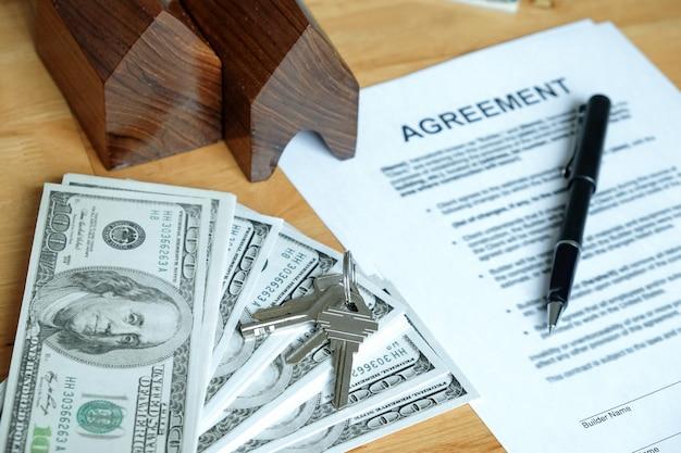 Dollar, model huis, huissleutels en pen op overeenkomst document.