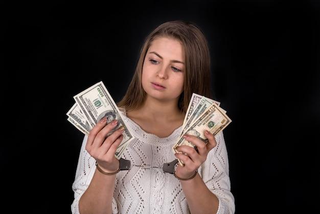 Dollar steekpenningen verdeeld in vrouw handen in handboeien