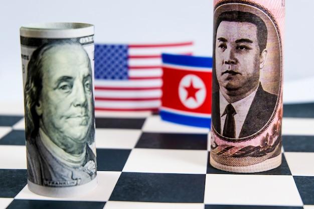 Dollarbankbiljet en bankbiljet van noord-korea met beide vlaggen van het land.