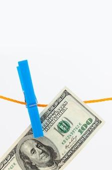 Dollarbankbiljetten bevestigd met wasknijpers aan een touw op een witte geïsoleerde achtergrond
