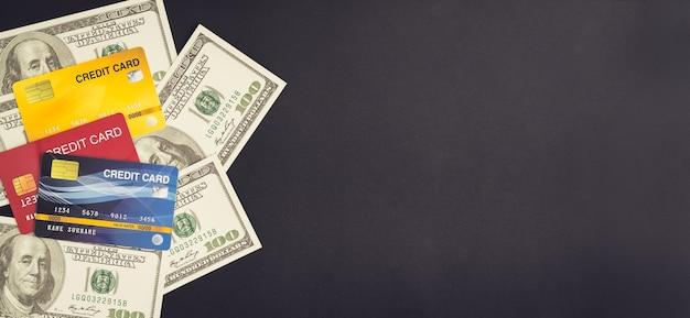 Dollarbiljetten en creditcards stapelen op zwarte achtergrond, geld groeiend concept en het doelsucces.