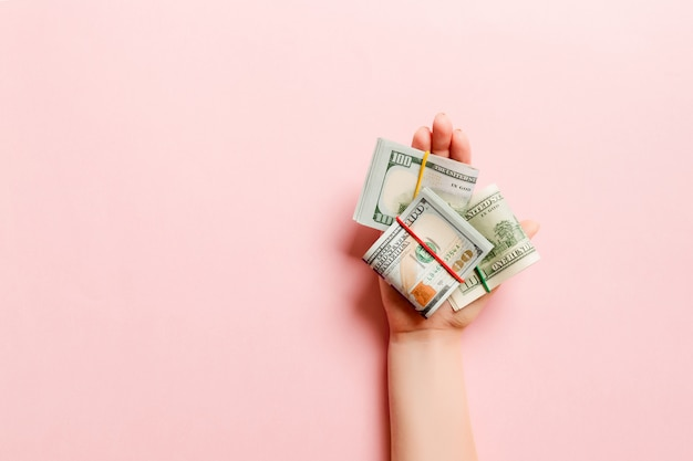 Dollarbiljetten in buizen in vrouwelijke hand op kleurrijke achtergrond