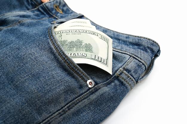 Dollarbiljetten in de voorzak van jeans, op een afgelegen witte achtergrond. hoge kwaliteit foto