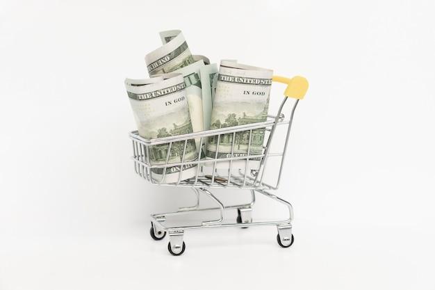 Dollarbiljetten in het winkelwagentje op witte achtergrond.