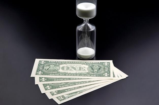 Dollarbiljetten liggen bij de zandloper. tijd is geld. het salaris. zakelijke oplossingen op tijd. zandloper tijdmeting