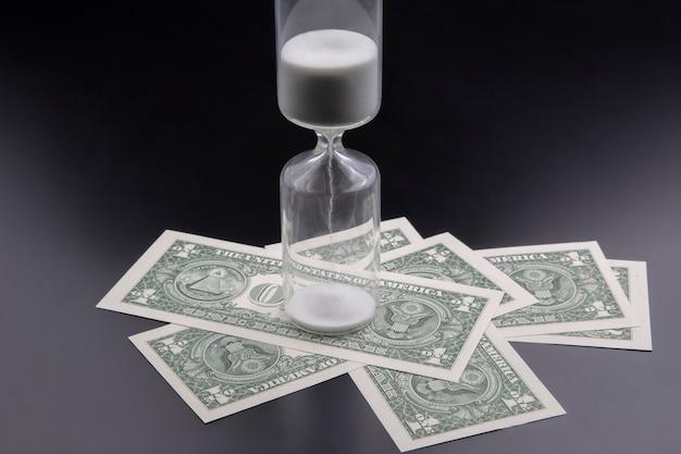 Dollarbiljetten liggen bij de zandloper.