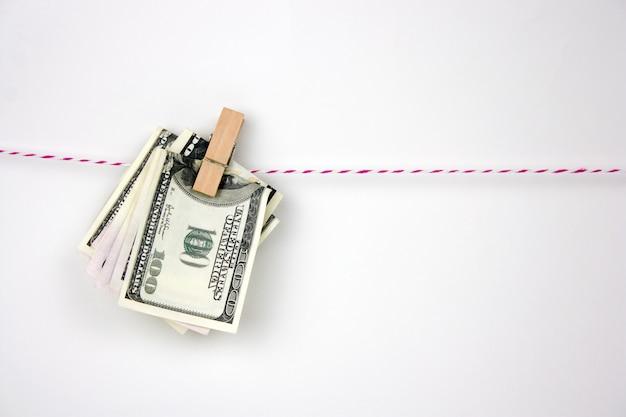 Dollarbiljetten met wasknijpers hangen aan een touw