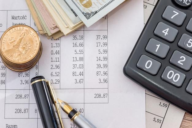 Dollarbiljetten met zakelijke documenten, pen en rekenmachine als achtergrond.
