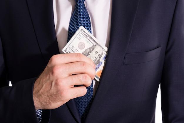 Dollarbiljetten zitten in de zak van het jasje van een zakenman