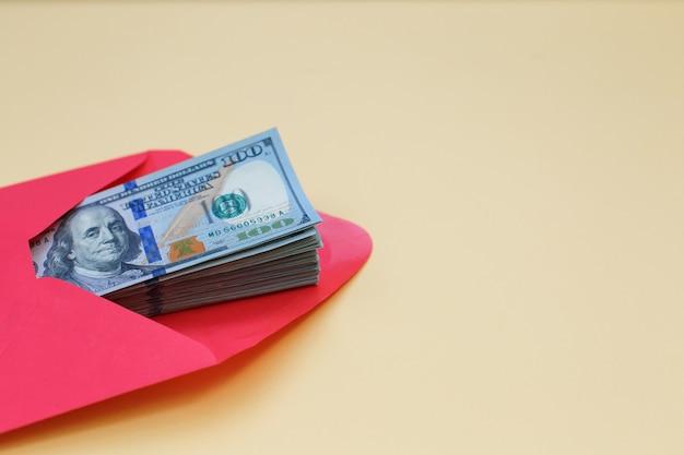 Dollargeld in de rode envelop. bonus, beloning, voordelen concept.