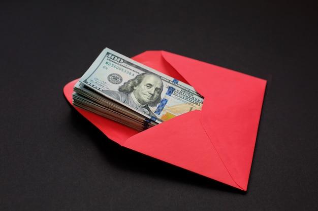 Dollargeld in de rode envelop op zwarte achtergrondbonus, beloning, voordelenconcept.