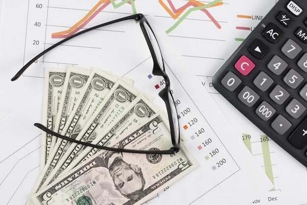 Dollarrekeningen, calculator en glazen op grafiekachtergrond.