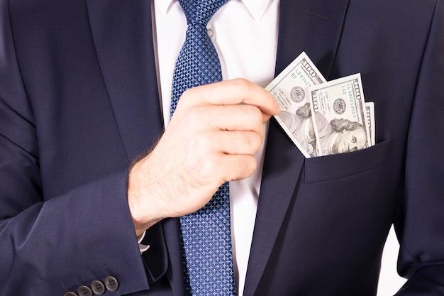 Dollarrekeningen in een jaszak van een zakenman. hand haalt een briefje van de amerikaanse dollar uit een zak van een jas