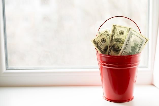 Dollarrekeningen in rode emmer. op witte window.light achtergrond.