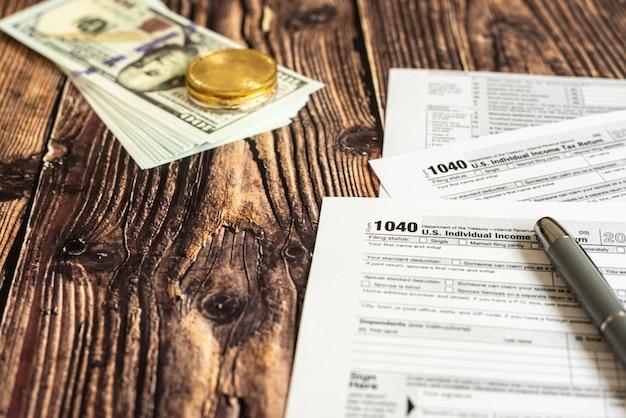 Dollarrekeningen op een tafel waarin het 1040 amerikaanse belastingbetalingsformulier is ingevuld.