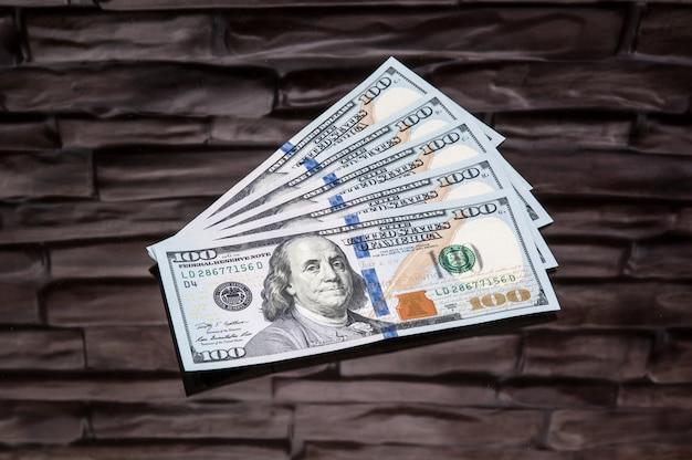 Dollars contant geldrekeningen op een baksteenachtergrond.