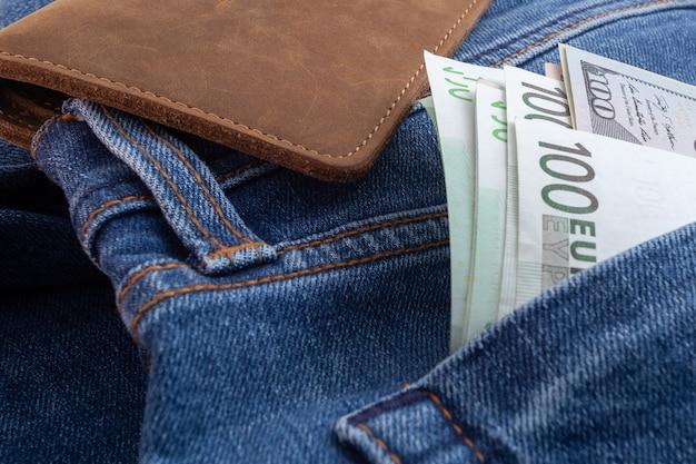 Dollars en euro steken uit jeanszak