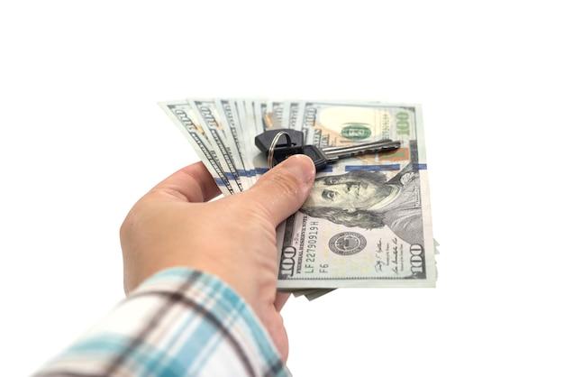 Dollars en sleutels in de hand. geïsoleerd op wit.