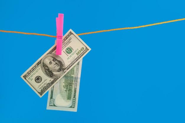 Dollars geld op touw wasknijper op blauwe achtergrond