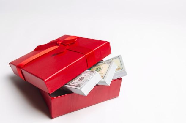 Dollars in een rode giftdoos op een witte achtergrond. zoek een cadeau voor de vakantie. cadeaubon