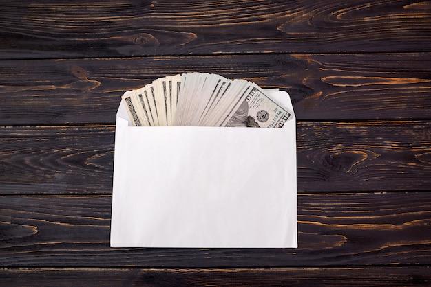 Dollars in een witte envelop op een houten achtergrond. uitzicht van boven.