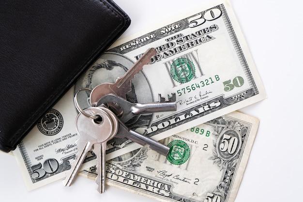 Dollars met sleutels op wit.