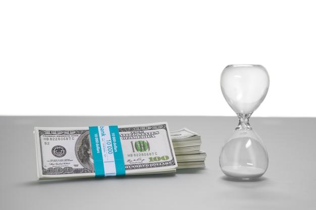 Dollars naast een zandloper. een moeilijke keuze. kies en los. eenvoudig maar aantrekkelijk.