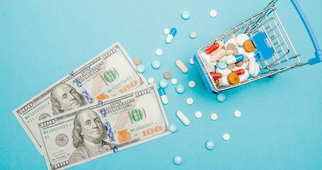 Dollars, pillen en winkelwagentje op een blauwe achtergrond. apotheek concept. kopieer ruimte.