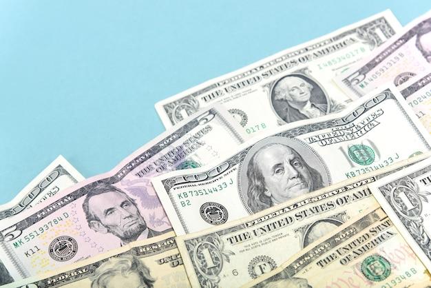 Dollars van verschillende coupures liggen op een lichtblauwe achtergrond