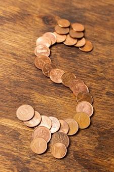 Dollarteken gemaakt van munten op houten achtergrond